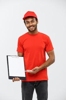 Pojęcie dostawy - portret przystojny mężczyzna dostawy afroamerykanów lub kuriera wykazujące potwierdzenie dokumentu formularza do podpisania. pojedynczo na tle szarym studio. skopiuj miejsce.