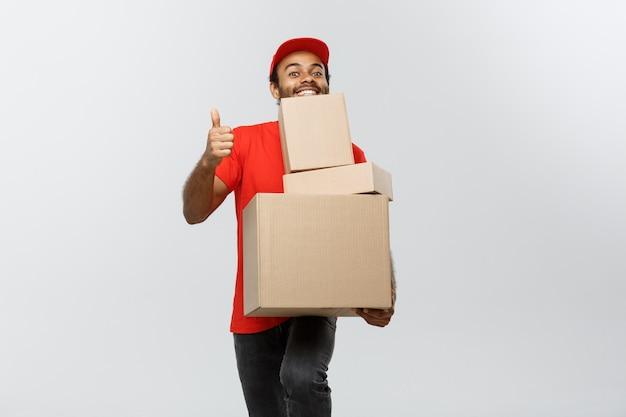 Pojęcie dostawy - portret szczęśliwego afroamerykanów dostawy mężczyzna w czerwonym szmatką gospodarstwa pakiet pudełko. pojedynczo na tle szarym studio. skopiuj miejsce.