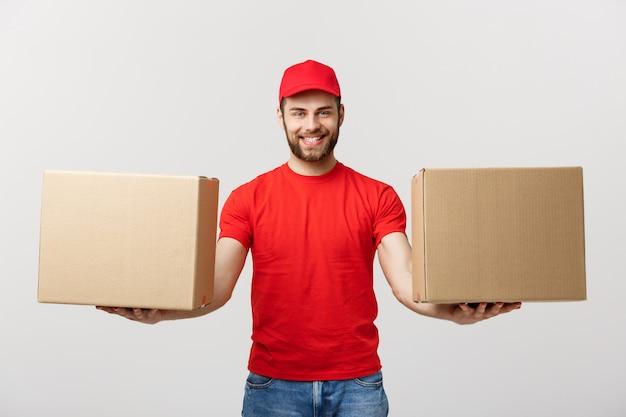 Pojęcie dostawy: portret uśmiechnięty doręczeniowy mężczyzna daje cardbox na biel ścianie.