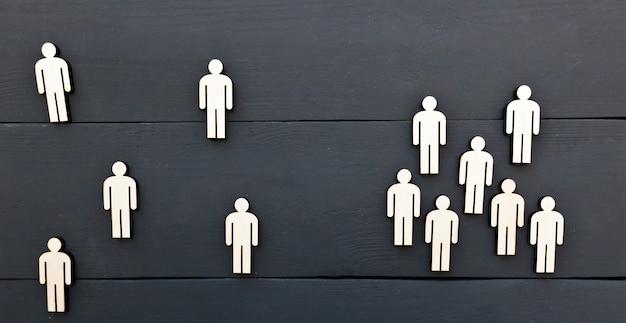 Pojęcie dystansu społecznego między ludźmi. jedna grupa osób drewnianych stoi osobno od osób z grupy anogrupowanej