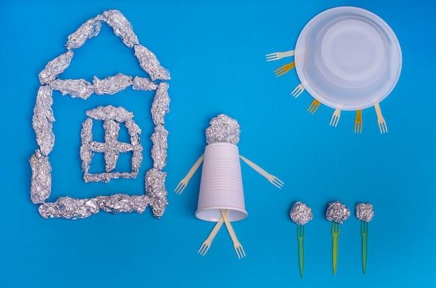 Pojęcie: ekologia, zanieczyszczenie środowiska. świat bez śmieci: dom, mężczyzna, słońce, kwiaty z folii i plastiku na niebieskiej powierzchni. oddzielna zbiórka śmieci.