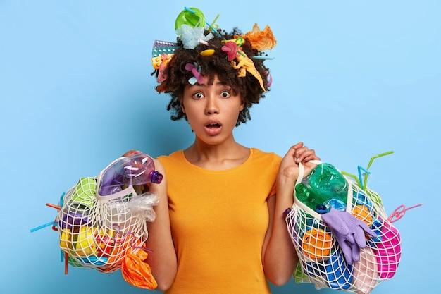 Pojęcie ekologii i środowiska. emocjonalna kobieta o ciemnej karnacji wspomaga redukcję śmieci