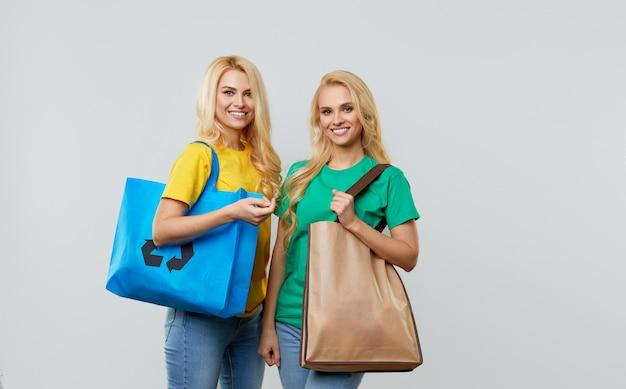 Pojęcie ekologii. młode kobiety w zwykłych ubraniach trzymają na ramionach ekologiczne torby z recyklingu.
