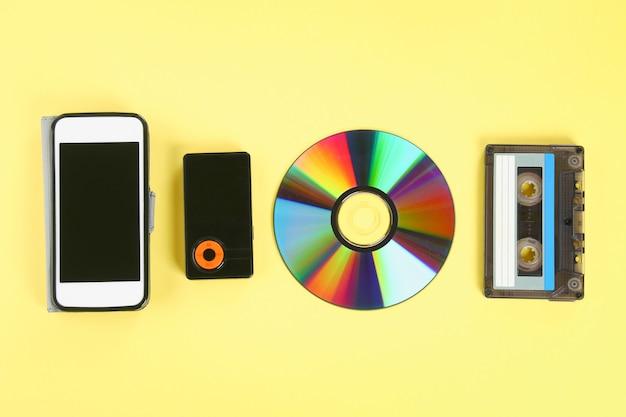 Pojęcie ewolucji muzyki. kaseta, dysk cd, odtwarzacz mp3, telefon komórkowy.