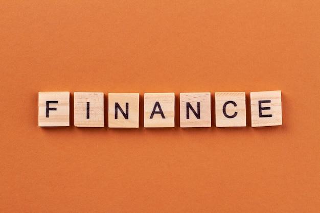 Pojęcie finansów i budżetu. bloki alfabetu z literami na białym tle na pomarańczowym tle.