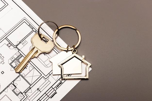 Pojęcie hipoteki i wynajmu mieszkań i nieruchomości. kredyty hipoteczne. metalowy brelok w kształcie domku z kluczem na planie domu. kupno domu.