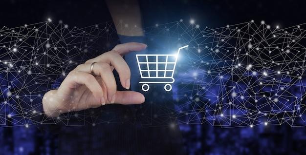 Pojęcie innowacji w e-commerce. ręka trzymać wózek cyfrowy z hologramem znak na ciemnym tle niewyraźne miasta. koncepcje zakupów online lub sklepu internetowego.