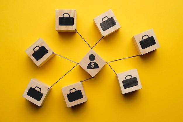 Pojęcie inwestora - abstrakcjonistyczna osoba z dolarem i komunikacja portfolio na drewnianych sześcianach.