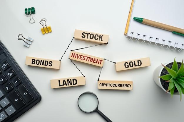 Pojęcie inwestowania w akcje, złoto, ziemię, kryptowalutę.