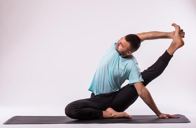 Pojęcie jogi. przystojny mężczyzna robi ćwiczenia jogi na białym tle na białym tle