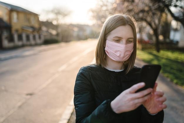 Pojęcie koronawirusa. dziewczyna czyta i ogląda wiadomości o koronawirusie przez telefon. mers-cov, powieść (2019-ncov). kobieta z medyczną maską twarzową, która szuka wiadomości za pomocą telefonu komórkowego. zanieczyszczenie powietrza.