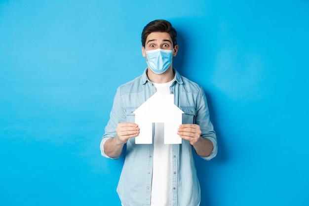 Pojęcie koronawirusa, kwarantanny i dystansu społecznego. młody mężczyzna szuka mieszkania, pokazuje model papieru domu, nosi maskę medyczną, wynajmuje lub kupuje nieruchomość, niebieskie tło.