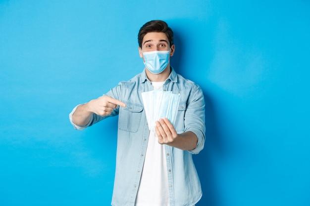 Pojęcie koronawirusa, kwarantanny i dystansu społecznego. stojący nad niebieskim tłem młody mężczyzna wskazujący na maski medyczne, zapobiegający zapobieganiu covid-19