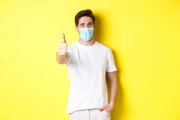 Pojęcie koronawirusa, pandemii i dystansu społecznego. pewny siebie młody człowiek w masce medycznej pokazując kciuki do góry i mrugając, żółte tło.
