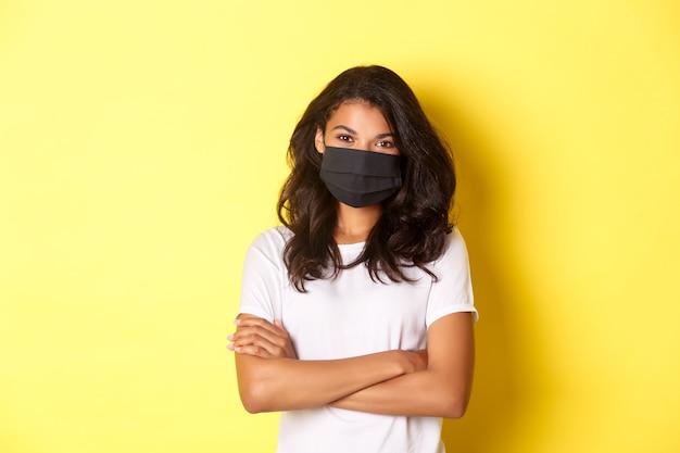 Pojęcie koronawirusa, pandemii i stylu życia. portret młodej kobiety afro-amerykańskiej w czarnej masce na twarz, uśmiechniętej i wyglądającej pewnie z rękami skrzyżowanymi na klatce piersiowej, żółtym tle.