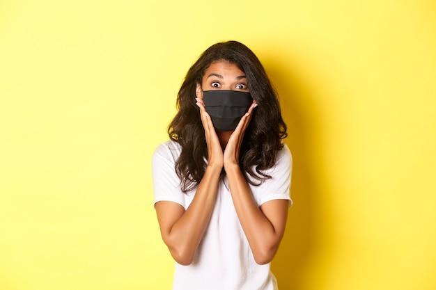 Pojęcie koronawirusa, pandemii i stylu życia. portret podekscytowanej afro-amerykańskiej kobiety w masce na twarz, patrzącej na coś fajnego, stojącej na żółtym tle