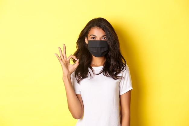 Pojęcie koronawirusa, pandemii i stylu życia. portret uśmiechniętej afro-amerykańskiej kobiety w masce na twarz, pokazującej w porządku znak w aprobacie, polecającej lub gwarantującej coś, żółte tło
