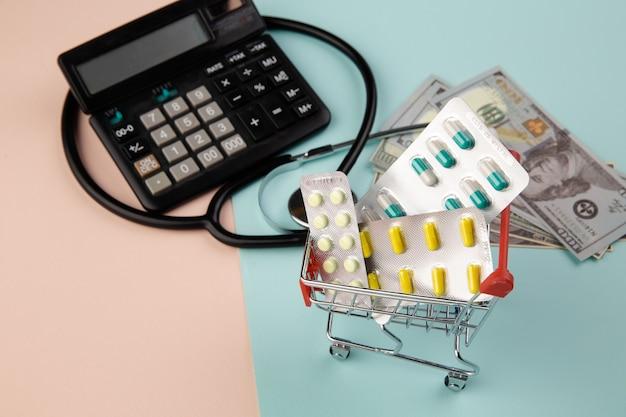 Pojęcie kosztów opieki zdrowotnej. stetoskop i narkotyki, banknoty pieniądze dolarów i kalkulator na kolorowym tle.