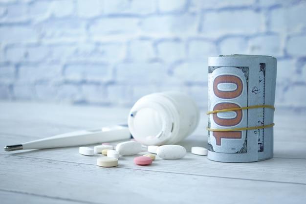 Pojęcie kosztów opieki zdrowotnej z nami dolara , pojemnik i tabletki na stole .