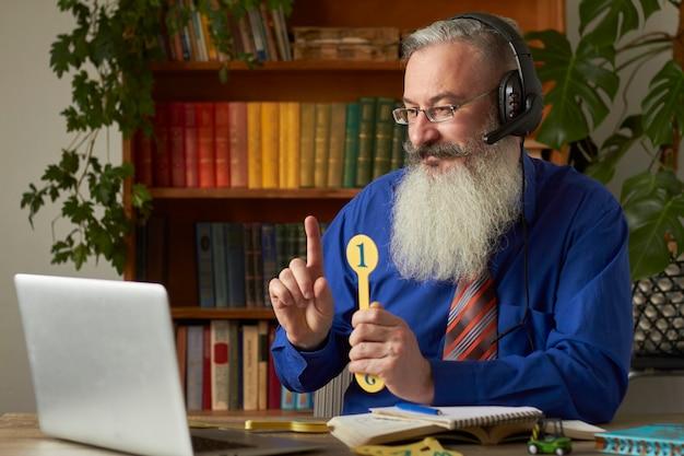 Pojęcie kształcenia na odległość dla małych dzieci. nauczyciel uczy dziecka czytania i liczenia online za pomocą laptopa.