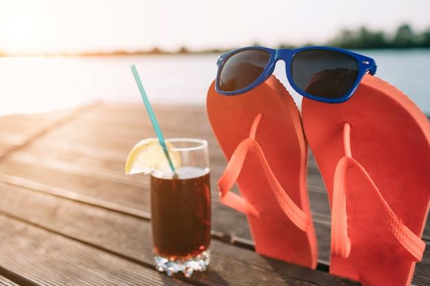 Pojęcie luksusowych wakacji. cola w szkle na drewnianym molo. różowe klapki z okularami przeciwsłonecznymi. impreza na plaży. czyste, błękitne niebo. poziomy, szeroki ekran.