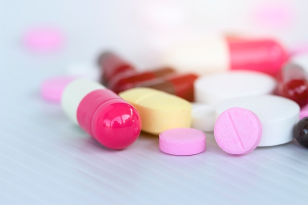 Pojęcie medycyny; wiele kolorowych leków. pigułki i kapsuły na białym tle