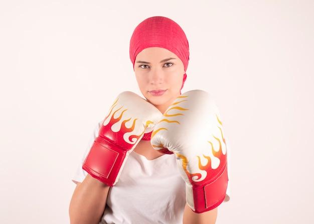 Pojęcie medyczne i zdrowotne. kobieta walcząca pokazująca rękawice bokserskie miesiąc świadomości raka piersi na białym tle