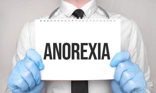 Pojęcie medyczne. lekarz pisze słowo anoreksja na białym papierze notatnika