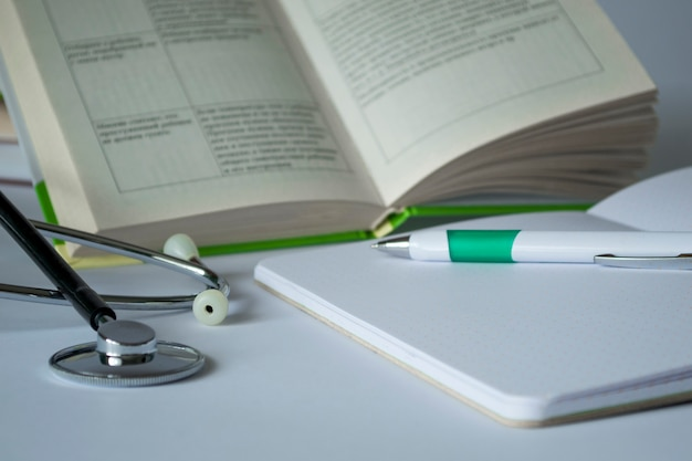 Pojęcie medyczne. na stole stetoskop, długopis, zeszyt, książka. wykształcenie medyczne na białym tle. przygotowanie do egzaminu, kompendium