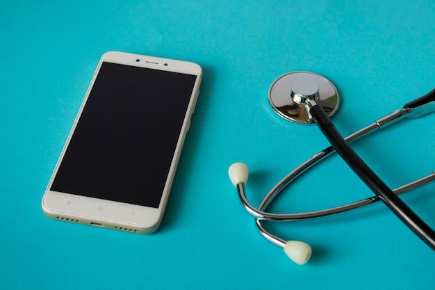 Pojęcie medyczne: stetoskop i telefon komórkowy na jasnym niebieskim tle. wezwanie do domu. ambulans. z miejscem na kopię.