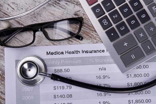 Pojęcie medyczne ubezpieczenia zdrowotnego. raport księgowy ze stetoskopem, kalkulatorem i okularami.