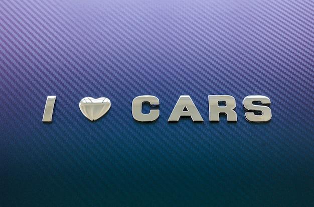 Pojęcie miłości do samochodów, jazdy. litery na powierzchni włókna węglowego