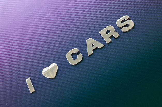 Pojęcie miłości do samochodów, motoryzacji. litery na tle z włókna węglowego
