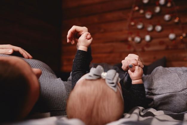 Pojęcie miłości i rodziny. dziewczynki delikatnie trzymając palce dorosłych na łóżku.