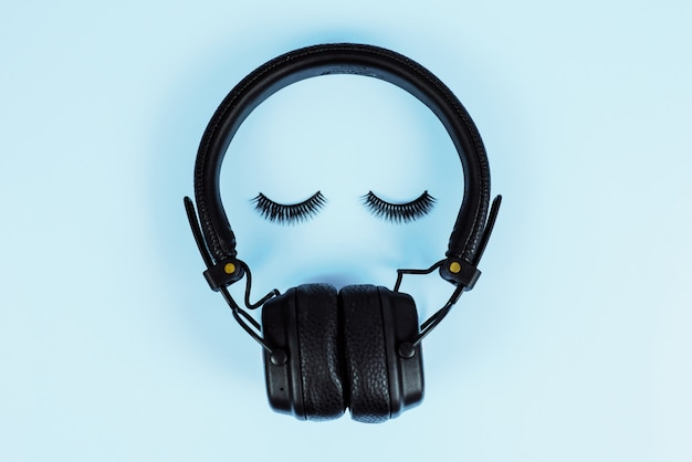 Pojęcie muzyki. koncepcja przedłużania rzęs. słuchawki bluetooth z sztucznymi rzęsami na niebieskim pastelowym tle