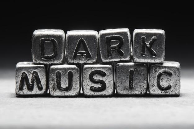 Pojęcie muzyki mrocznej. napis na metalowych kostkach 3d na białym na czarnym tle, styl grunge