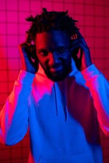 Pojęcie muzyki murzyn słucha muzyki w słuchawkach na tle neonowego światła czerwonego i niebieskiego