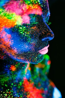 Pojęcie. na ciele dziewczyny pomalowana talia dj-a. półnaga dziewczyna malowana w kolorach uv.