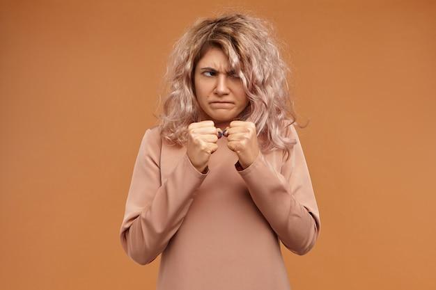 Pojęcie negatywności, agresji i wściekłości. zabawna, emocjonalna młoda kobieta rasy kaukaskiej marszczy brwi, trzymając przed sobą zaciśnięte pięści, gotowa do uderzenia wroga