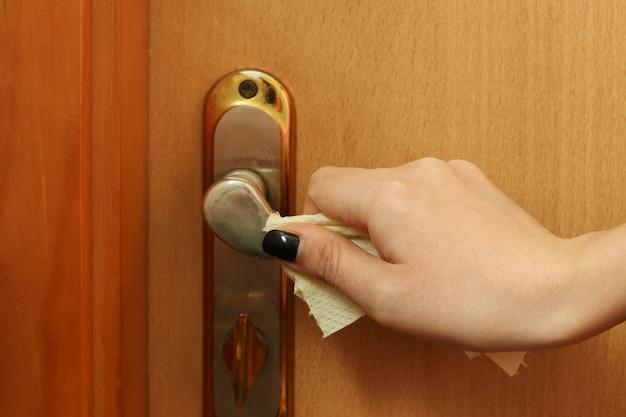 Pojęcie niebezpieczeństwa infekcji podczas pandemii koronawirusa covid-19. klamka jest owinięta papierem toaletowym dla ochrony, zbliżenie