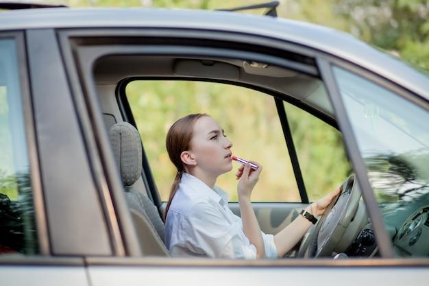 Pojęcie niebezpieczeństwa jazdy. młoda kobieta kierowca rudowłosa nastolatka maluje usta robi stosowanie makijażu podczas jazdy samochodem.