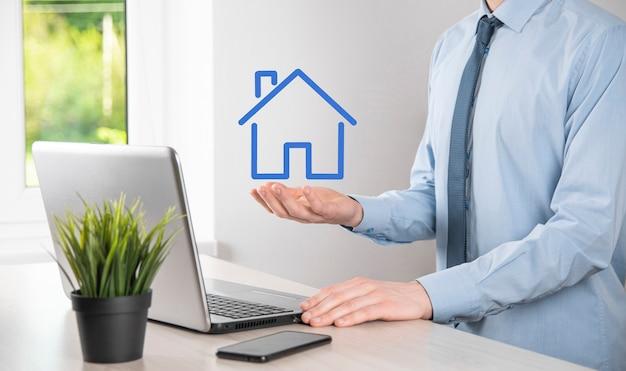 Pojęcie nieruchomości, biznesmen posiadający ikonę domu. dom na rękę. koncepcja ubezpieczenia i bezpieczeństwa nieruchomości. ochronny gest człowieka i symbol domu.