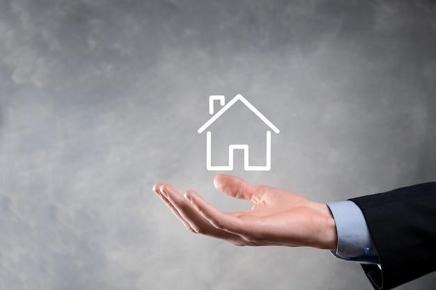 Pojęcie nieruchomości, biznesmen posiadający ikonę domu.