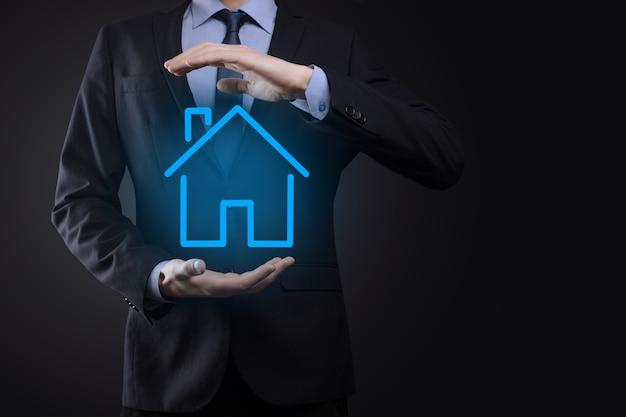 Pojęcie nieruchomości, biznesmen z ikoną domu. dom pod ręką. koncepcja ubezpieczenia i bezpieczeństwa nieruchomości. ochronny gest człowieka i symbol domu.
