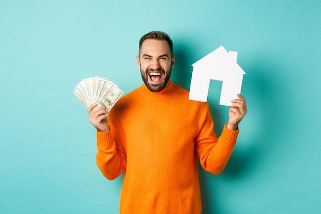 Pojęcie nieruchomości i koncepcja kredytu hipotecznego. ekstatyczny kaukaski mężczyzna trzyma dolary pieniędzy i maket domu, krzycząc z radości, stojąc na niebieskim tle.