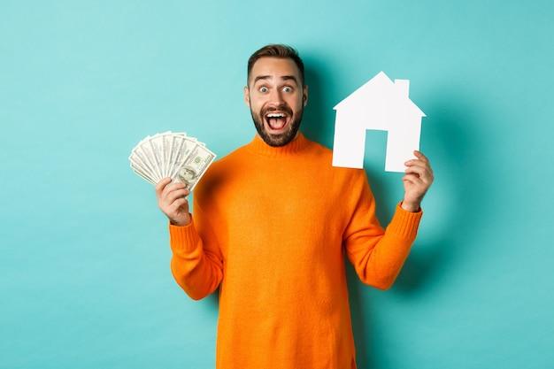Pojęcie nieruchomości i koncepcja kredytu hipotecznego. podekscytowany mężczyzna pokazuje dolary i maket papieru domu