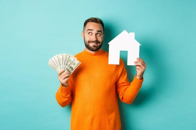 Pojęcie nieruchomości i koncepcja kredytu hipotecznego. przystojny młody mężczyzna kupuje dom, trzymając w domu maket i pieniądze, myśląc i uśmiechając się, stojąc na jasnoniebieskim tle.