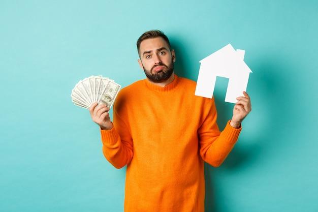 Pojęcie nieruchomości i koncepcja kredytu hipotecznego. smutny i zdezorientowany mężczyzna pokazujący pieniądze i makietę z papieru, wzruszający ramionami, stojący na jasnoniebieskim tle.