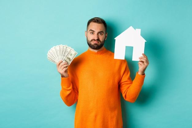 Pojęcie nieruchomości i koncepcja kredytu hipotecznego. smutny mężczyzna pokazujący maket i pieniądze, wyglądający na zdenerwowanego i rozczarowanego, stojący na jasnoniebieskim tle.