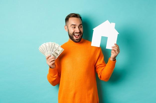Pojęcie nieruchomości i koncepcja kredytu hipotecznego. wesoły mężczyzna trzymający pieniądze i papierowy dom, uśmiechnięty podekscytowany, kupujący lub wynajmujący mieszkanie, stojący na niebieskim tle.